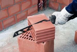 строитель режет сабельной пилой кирпич