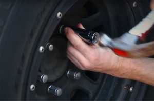ржавый болт на диске машины отбивают молотком